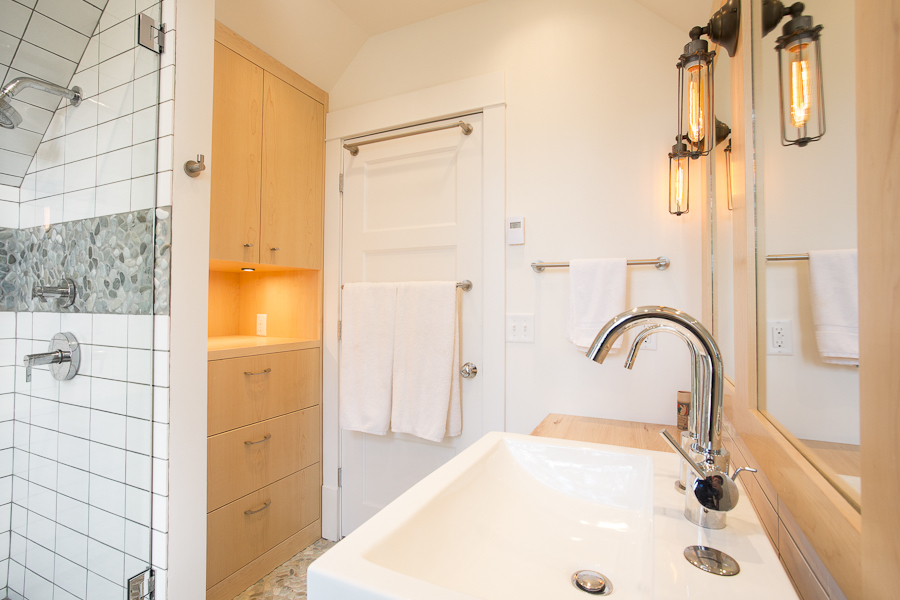bathroom utilizes low-flow fixtures, locally sourced Dutch Elm countertops, and a natural stone pebble mosaic floor.