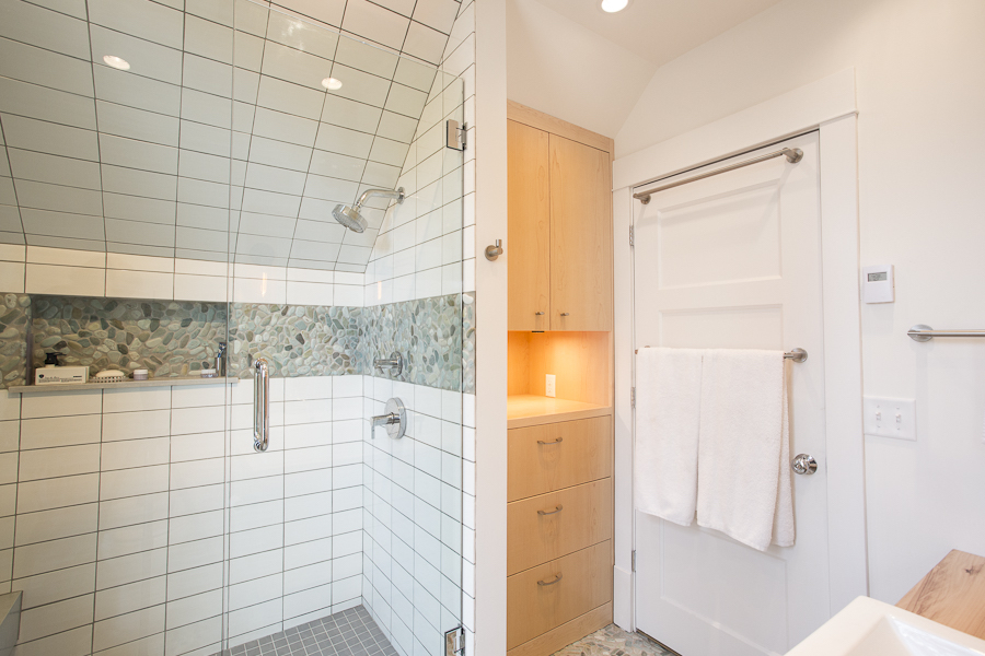 Bathroom with low-flow fixtures, locally sourced Dutch Elm countertops, and a natural stone pebble mosaic floor.