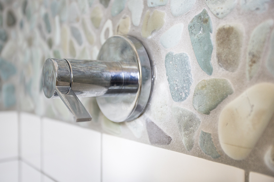 Third-floor alcove shower features a low-flow showerhead and an accent strip of the same natural stone mosaic