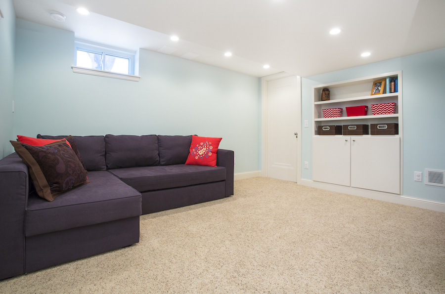 Sectional in basement with light blue walls and tan carpeting