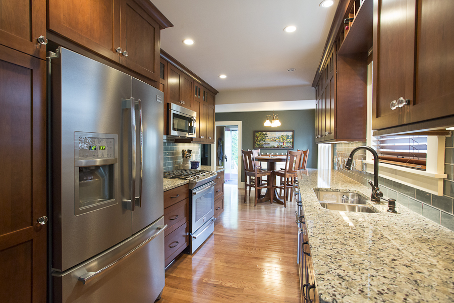 Kitchen with walnut cabinets and tan granite countertops
