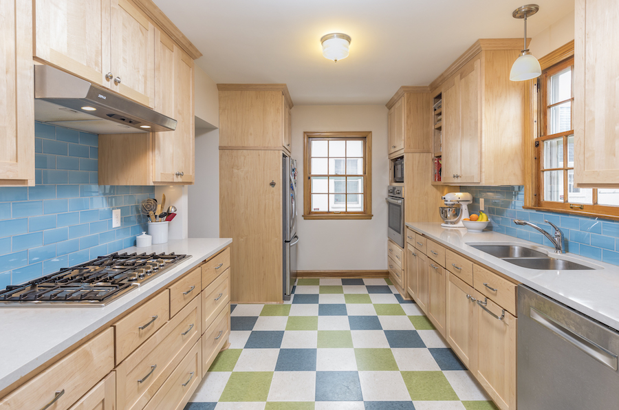 Kitchen with maple cabinets and green, white, and blue tile floor