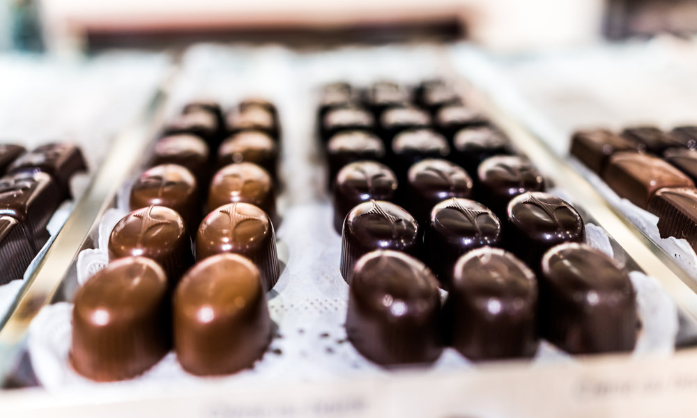 Shiny-smooth-gourmet-chocolate-truffles-on-a-tray-in-bakery-699423450_4146x2493.jpeg