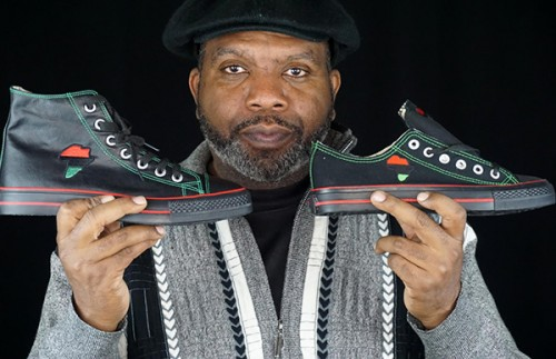 Tariq Edmonson, founder of SneakersCustom.com, poses with his custom-designed African sneakers