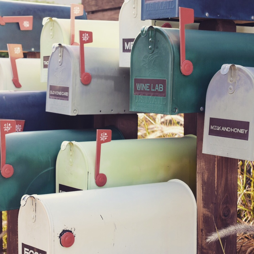 The cutest array of mailboxes with each storefront name.