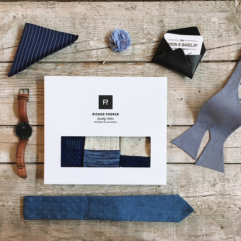 Dibi Silk Pinstripe Pocket Square - $20 In Store Only   Loyal Stricklin Envelope Wallet  - $30  Dibi Floral Lapel Pin - $30 In Store Only  Dibi Cotton Rayon Self-Tie Bow Tie - $37 In Store Only   Richer Poorer Deep Blue 3-Pack Socks  - $38   18 Waits The Tie Starlight  - $70  Daniel Wellington Classic Black Durham in Silver - $229 In Store Only