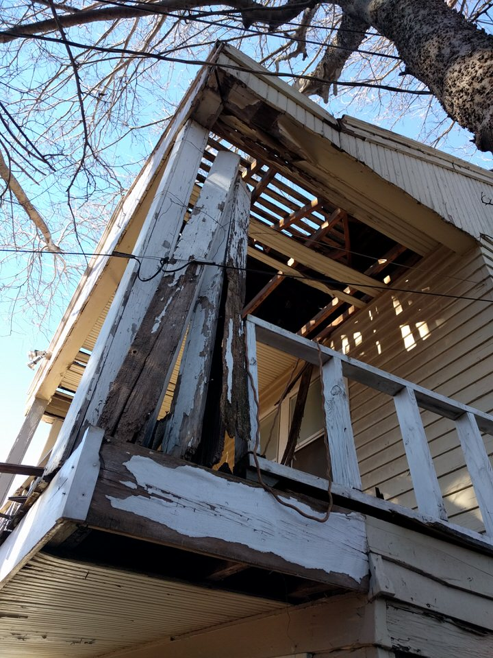 A long neglected balcony on the historic carriage house. This carriage house was in the process of becoming declared dilapidated when Red Door Investments purchased the property.