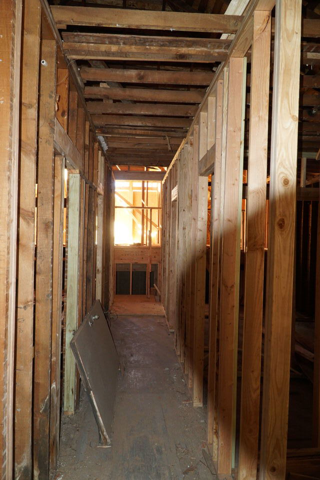 Looking north from kitchen/living through future hallway. Upper level flooring of split level addition is visible beyond.