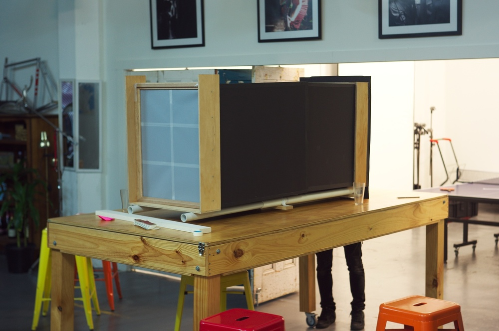 Our half finished 20×24 camera sitting on a table on wheels (makes a nice stand!), sitting ready to test out the lens…