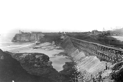 The San Vicente Creek trestle being filled in, 1906. If you look closely you can see the fledgling cement plant in the distance on the right. So, the first thing you should remember is that inside each of those ramparts is the skeleton of the trestle that was buried almost a century ago. The trestles were built first to provide a framework for the fill material, helping to contain the materials when they were dumped as well as guiding the pile with a uniform slope on either side. Besides, imagine how difficult it would be to get the materials from each side of the canyon to the middle without the trestle from which to dump it.
