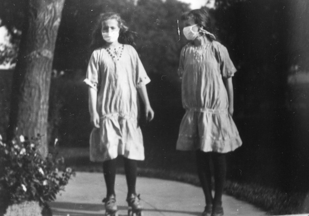 "This photograph from the McLean family collection shows Hulda Hoover and her sister Louise roller skating in Palo Alto during the 1918-1919 pandemic.   When I asked Hulda (we knew her as Hulda Hoover McLean) about this photograph she remembered  the masks as being ""scratchy"" and ""uncomfortable"".  Photo credit: McLean family collection."