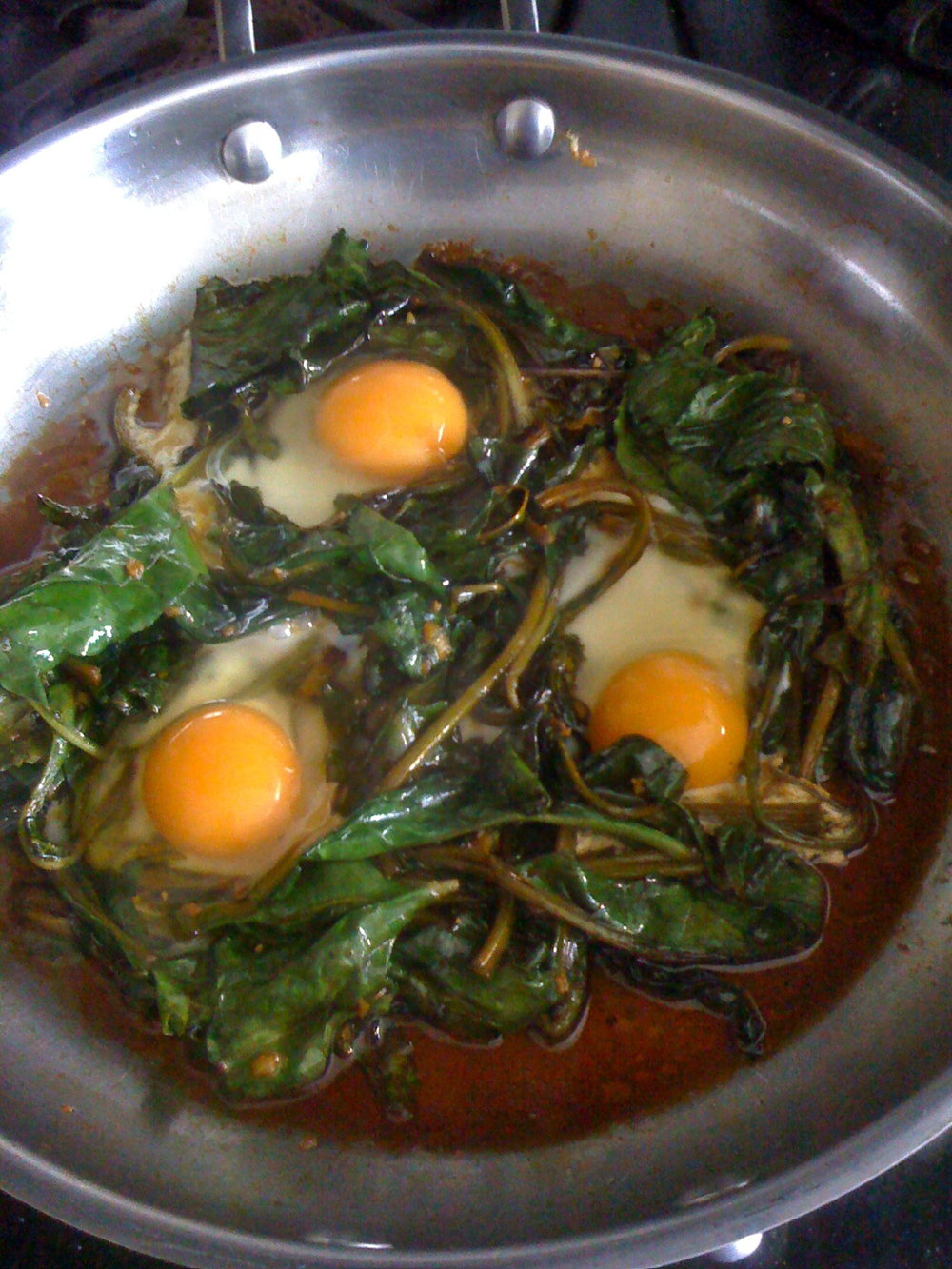 Sunny-side eggs in sauteed greens