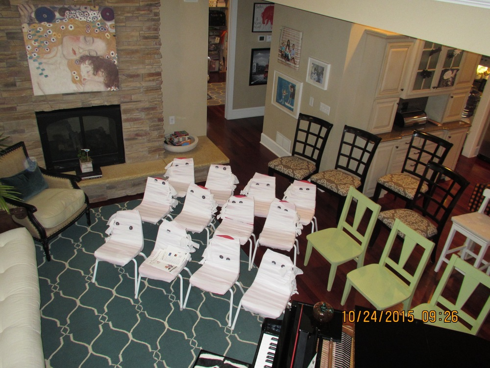 Twelve chairs wrapped up as mummies waiting for the pianists.