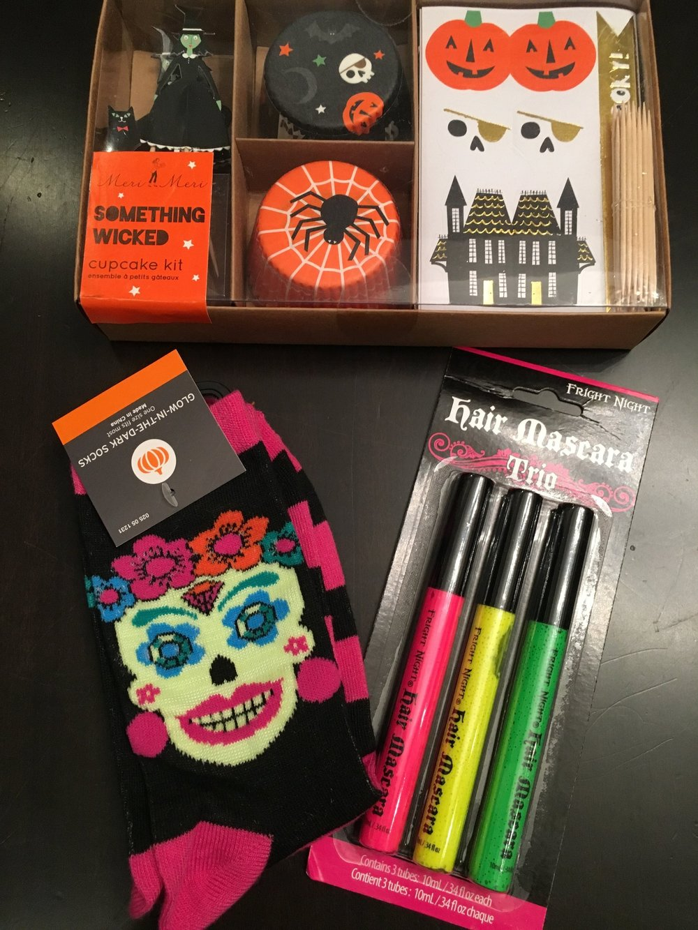 """My daughter is dressing up as a Harry Potter Gryffindor student (thank you for not confusing her with Hermione). Her  pinch  includes:hair mascara, a cupcake kit and some """"smell my feet"""" Day of the Dead socks."""