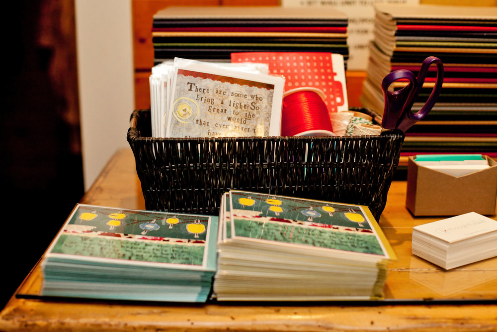 This is how the journals were set up for the breakfast event. There was a choice between two sympathy cards and the journals were stacked to display all the colors to choose from. A basket with ribbon was available to wrap the  thoughtful pinch so that it was ready to go.  Photo Credit -Bethany Meister:Photographer.