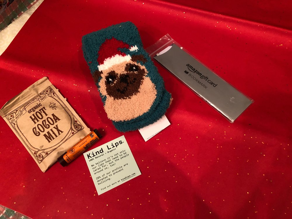 """This was the """"Chill Kit"""": A packet of hot cocoa, Kind Lip Balm, soft socks, a candy cane and the Amazon gift card in the form of a book marker."""