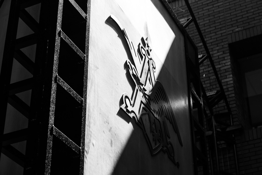Bright sun and dark shadow produce lovely contrast over the  Anheuser-Busch logo.