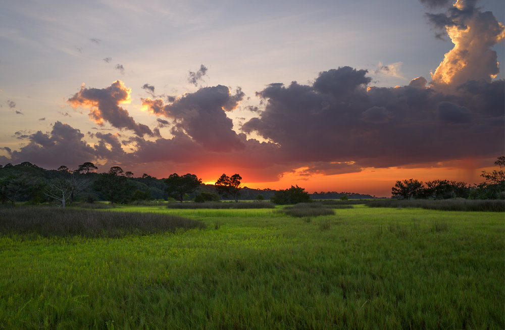 Big fluffy clouds, intense orange sunset and bright green grass - your typically experience at Jekyll Island, Georgia.