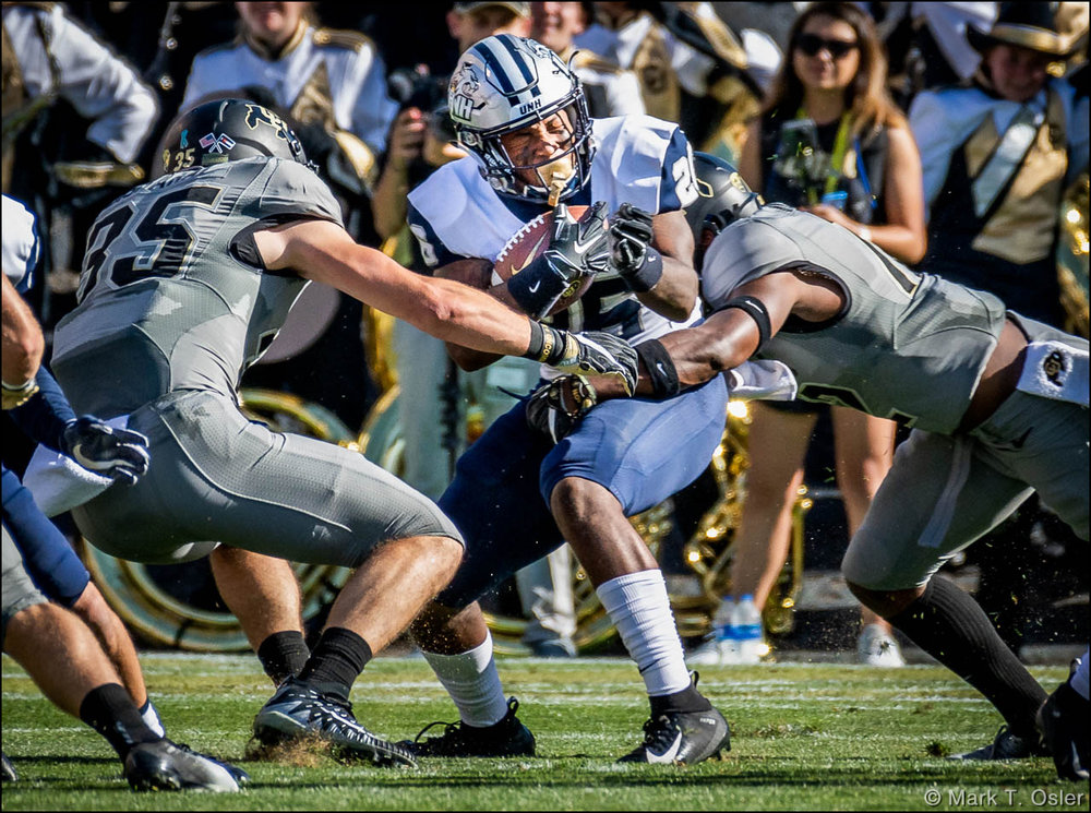 UNH kick returner Carlos Washington, Jr. (#26) winces as he is hit by CU safety Hasaan Hypolite (#12) and tailback Beau Bisharat (#35) during a kickoff return in the second quarter. Washington returned the ball to the UNH 10 yard line before being stopped.