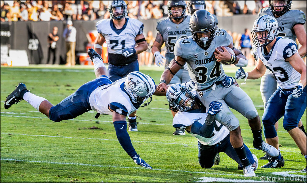 With UNH linebacker Quinlen Dean (#4, in air, left) pursuing, UNH safety Pop Lacey (#40) takes down CU tailback Travon McMillian (#34) after a 12-yard gain midway thru the third quarter.