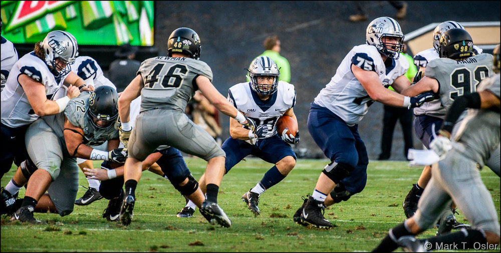 UNH running back Brandon Gallagher (#29) looks for an opening in the CU defense. CU defensive back Chase Newman (#46) defends on the play.