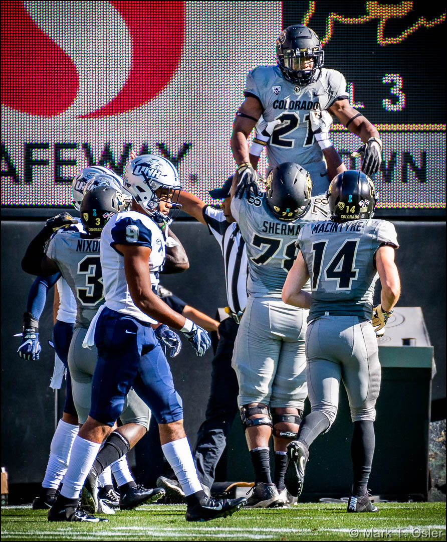 UNH cornerback Isiah Perkins (#9) walks past CU celebration as CU offensive lineman William Sherman (#78) hoists tailback Kyle Evans (#21) in the air after Evans rushed for a six-yard touchdown for the Buffs in the second quarter.