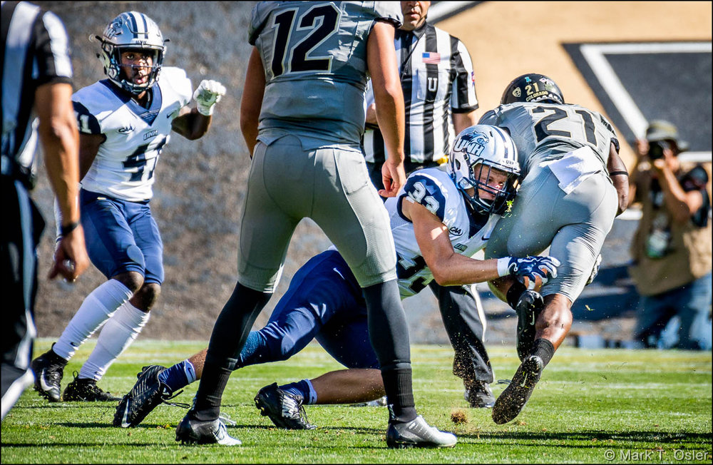 UNH safety Evan Horn (#33) takes down CU tailback Kyle Evans (#21) after one of Evans' three consecutive rushing gains early in the second quarter. UNH cornerback Alonzo Addae (#41, left) closes in on play.