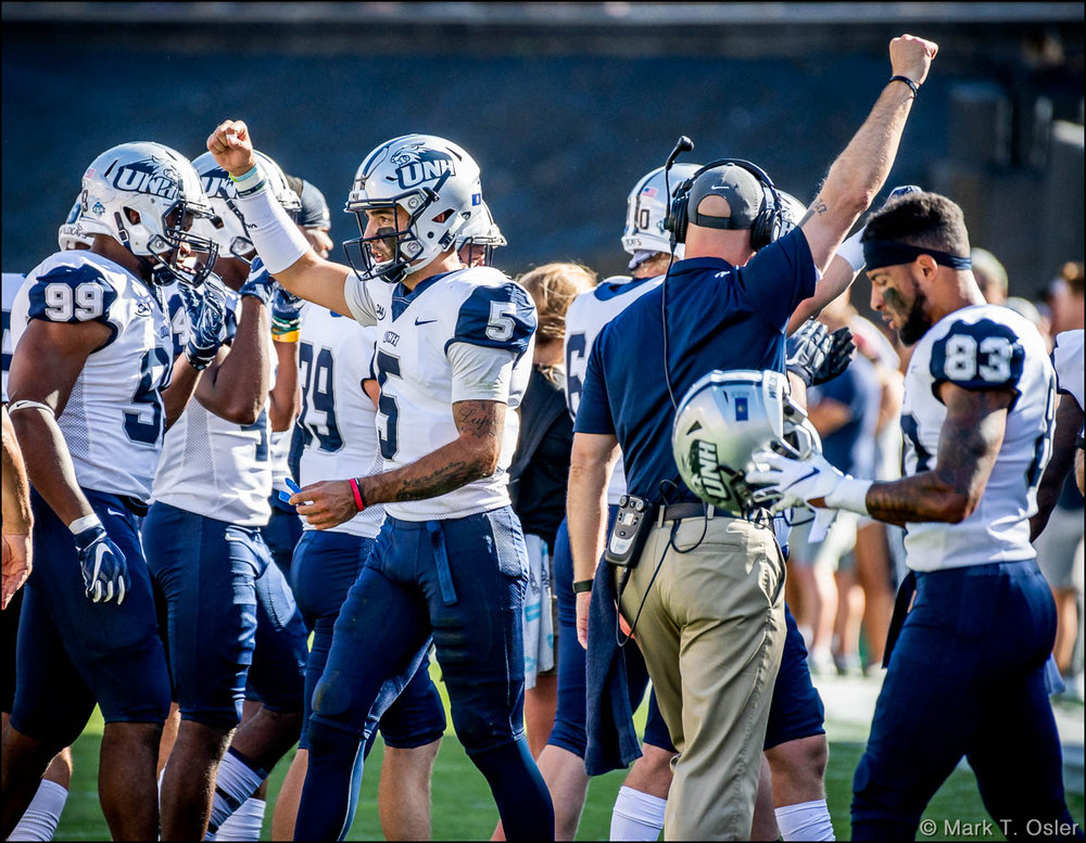 UNH quarterback Christian Lupoli (#5) and coach Garrett Gillick raise their fists to celebrate the overturning of a fumble call that would have given CU possession of the ball in the second quarter.