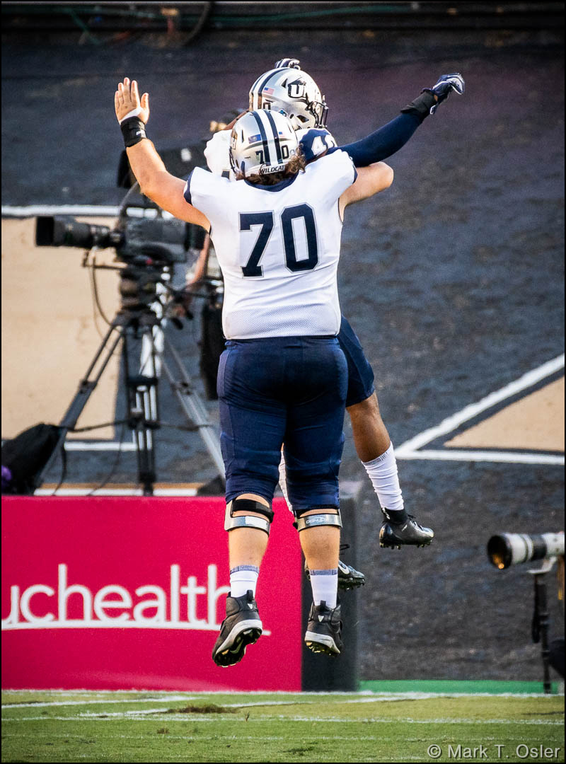 UNH offensive lineman Matt Mascia (#70) has a leaping celebration with UNH safety Pop Lacey (#40) after Lacey put UNH on the scoreboard, returning an interception 15 yards for a touchdown early in the third quarter.