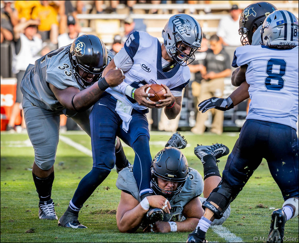 UNH quarterback Christian Lupoli is sacked for a 6-yard loss by CU defensive tackle Javier Edwards (#33) and defensive end Mustafa Johnson (#34, on ground) on UNH's first play of the third quarter.