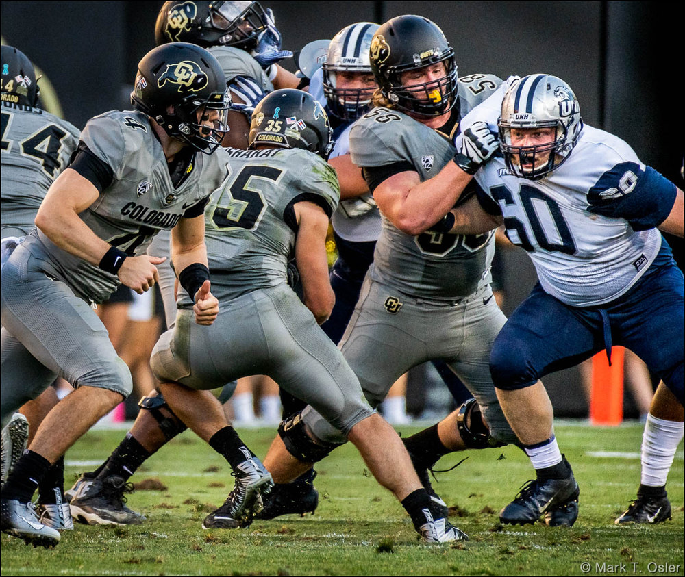 UNH defensive tackle Jacob Bradshaw (#60) stands his ground against CU offensive lineman Kary Kutsch (#58) to contain CU tailback Beau Bisharat (#35) in the fourth quarter.