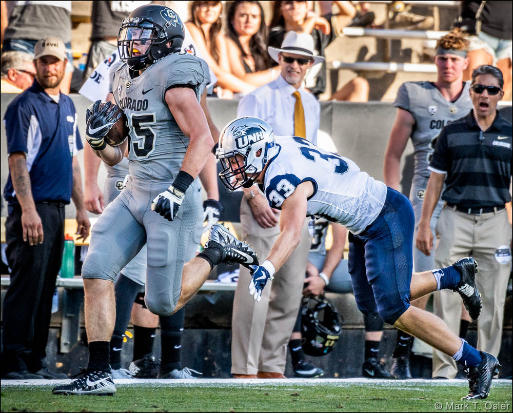 UNH safety Evan Horn (#33) dives to get a hand on the left foot of CU tailback Beau Bisharat (#35) and prevent a CU touchdown midway thru the third quarter. Bisharat gained 47 yards on the play.