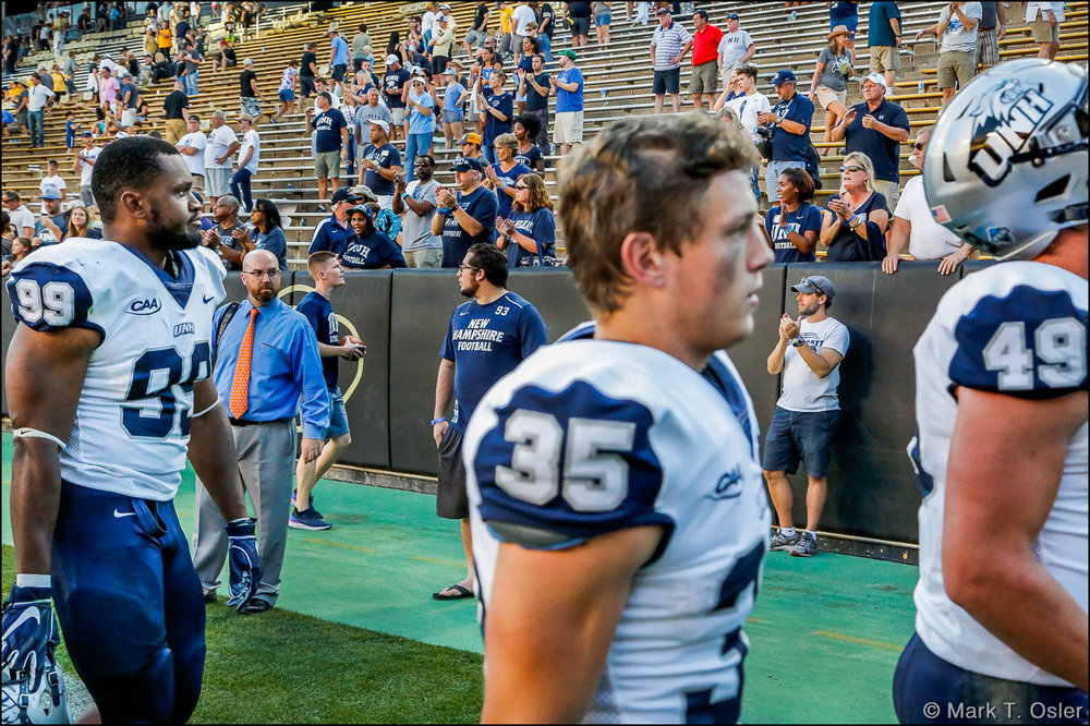 UNH faithful stayed to the bitter end to cheer the efforts of their Wildcat football team as players leave the field following the team's 45-14 loss to the University of Colorado Saturday, Sep. 15, 2018 in Boulder, CO. Leaving the field (l. to r.) are UNH defensive end Brian Carter (#99), wide receiver Sean Coyne (#35) and tight end Gunner Gibson (#49).