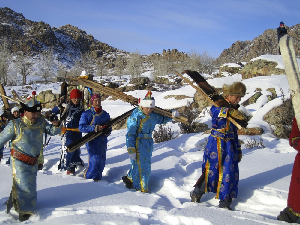 Traditional skiers from the Altay region of Xinjiang, China, during the Altay Ski History Conference.  The fur covered skins on their skis facilitate glide on the exceptionally cold snow of the region, and don't need to be removed before descending.