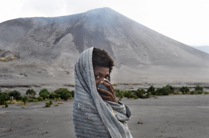 A boy shields his face from volcanic dust whipped up by the cyclone. Mt Yasur, Tanna Island.