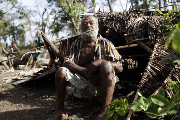 Village chief Philip Kasamu sits beside his destroyed hut. Tanna, Island.