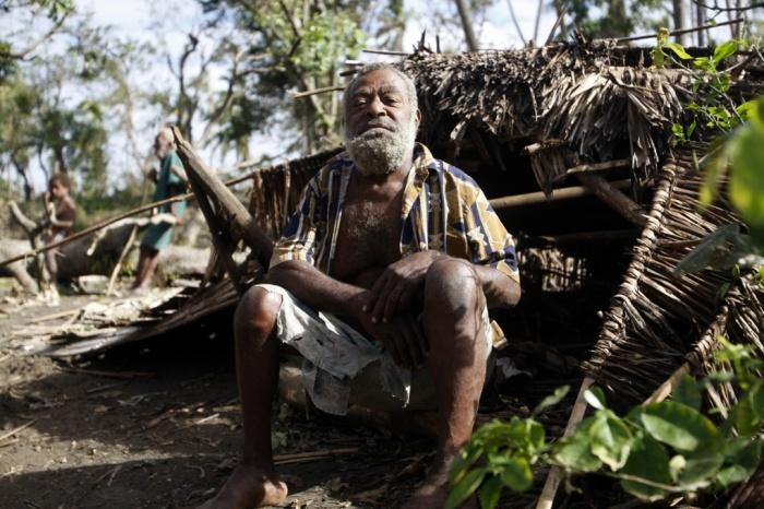 Village chief Philip Kasamu sits beside his destroyed hut. Tanna, Island.