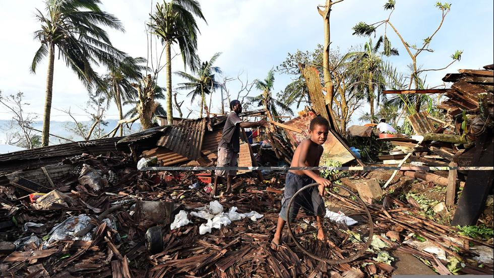 Samuel and his father Philip search through the ruins of their home on 16th March, 2015. Port Villa.