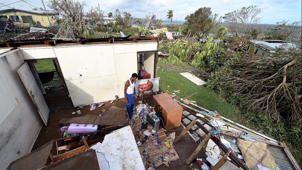 Uwen Gaere surveys his destroyed house on 16th March, 2015. Port Villa.