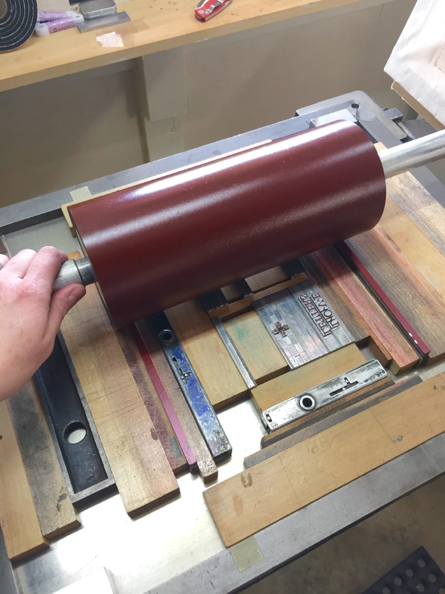 Rolling the red ink onto the type...