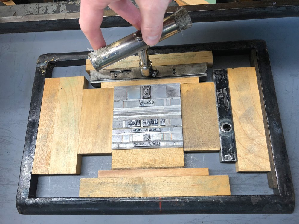 Turning the quoins, or locks, to tighten the whole forme in the chase.