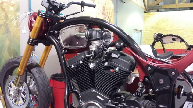 Air is gulped through a custom K&N airbox (with a purported 40% increase in volume over a typical side-induction system) and injected with fuel to feed the 2032cc S&S Cycle T124 V-Twin motor. Arch claims a healthy 121.5 horsepower and 121.8 lb-ft at the rear wheel. The arched-backbone frame tube is a neat trick of a steel tube inside a tube. The rear section of the frame (in black) is a chunk of billet aluminum.