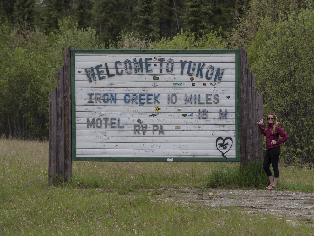Megan celebrating at the Yukon sign off the Alaskan Highway.
