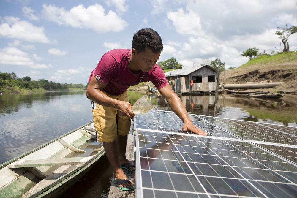 Mamirauá, AM, 27 de outubro de 2015 - Iane fazendo manutenção do sistema de bombeamento de água do rio para sua casa, que funciona com energia do sol, facilitou suas tarefas domésticas. Agora as pessoas não precisam mais descer até a beira  do rio várias vezes por dia. (©Greenpeace/Otávio Almeida)