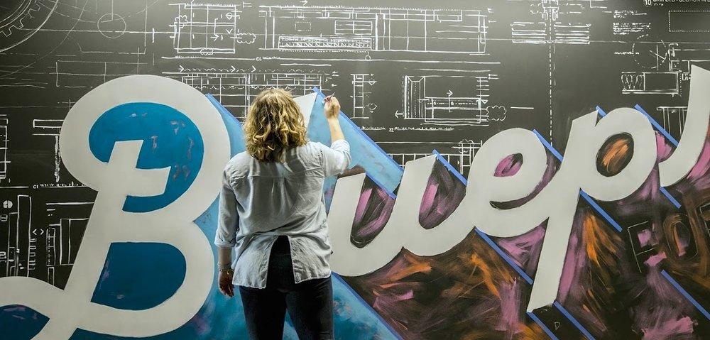 Amanda Paulson painting mural for Skender Construction