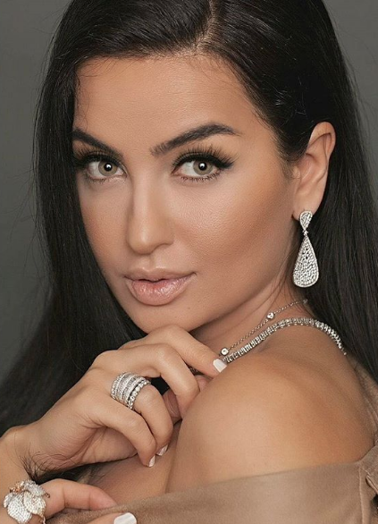 - Gina Amir wearing a custom Diamond drop earrings and stackable diamond eternity bands.
