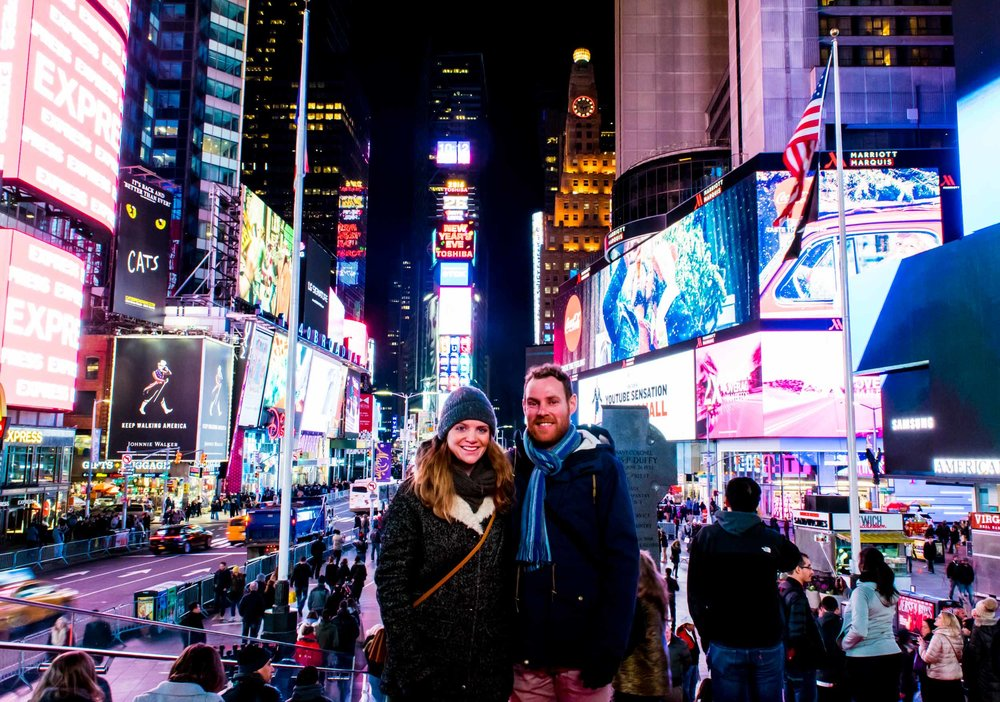 Couple stood in New York's Times Square with huge billboards behind them.