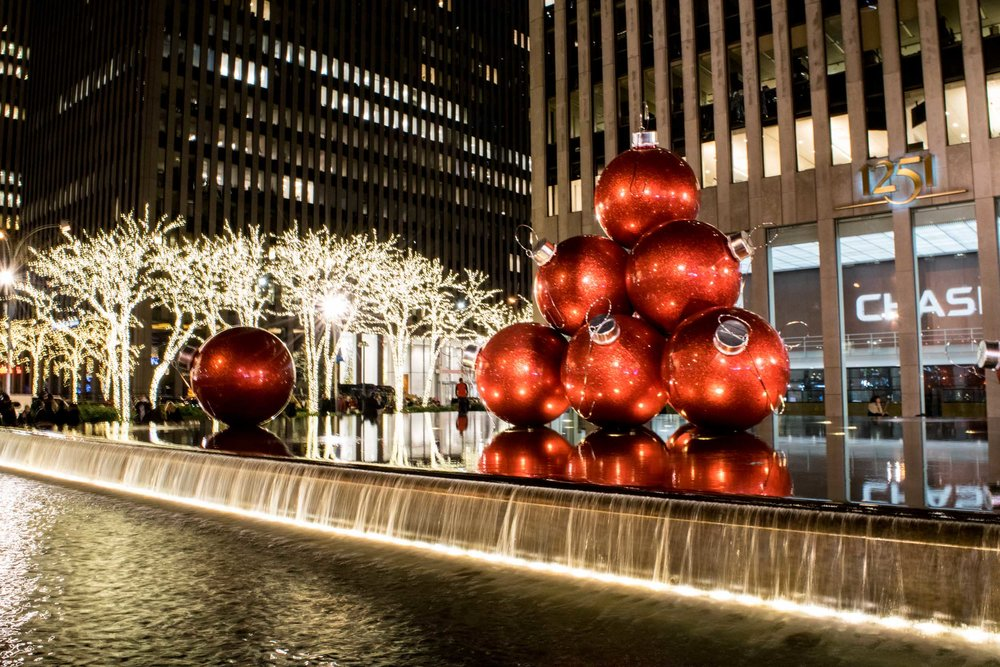 Chase Bank's Christmas display with giant red baubles in a water fountain.