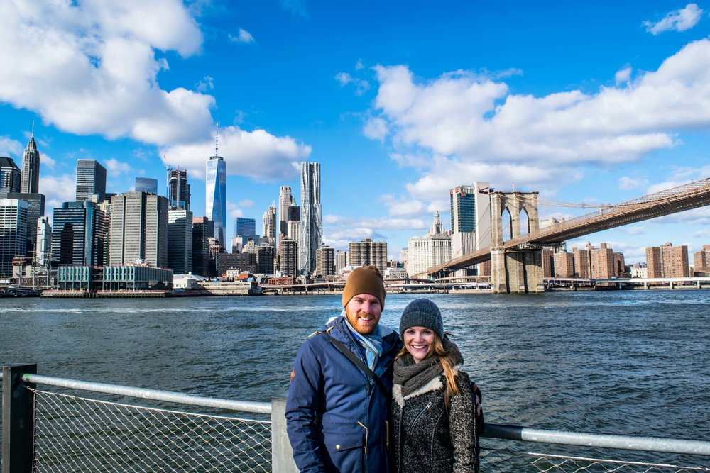 Couple in Dumbo with Brooklyn Bridge and Manhattan skyline behind.