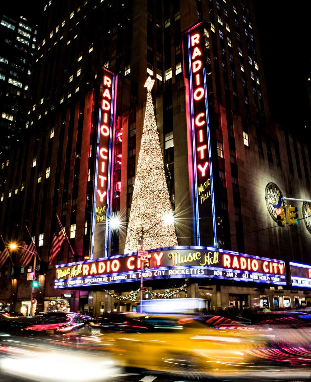 Radio City Music Hall showing the Christmas Spectacular starring the Rockettes with the blur of New York traffic and yellow taxi cabs below.